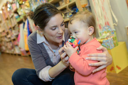 mother and daughter with attractive vendor in toy store Stock Photo