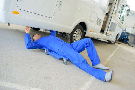 Mechanic laid on trolley under motor home