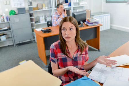 dissident: Lady at desk, shrugging Stock Photo