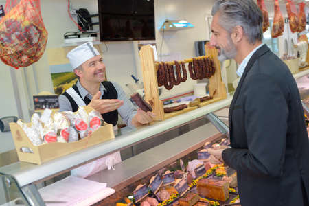 congenial: Suited man being served by butcher Stock Photo