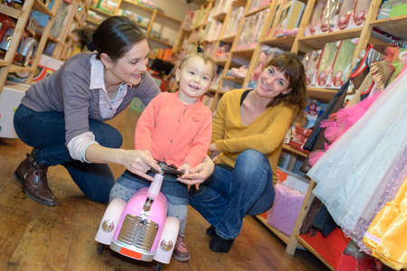 truck driver: mother and daughter with attractive vendor in toy store Stock Photo