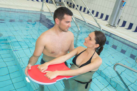 Pregnant woman holding float in swimming pool