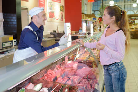 siervo: Customer being served at meat counter Foto de archivo
