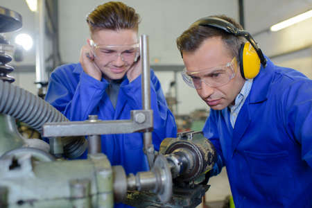 Apprentice covering his ears against noisy machine