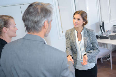 Woman welcoming couple into office