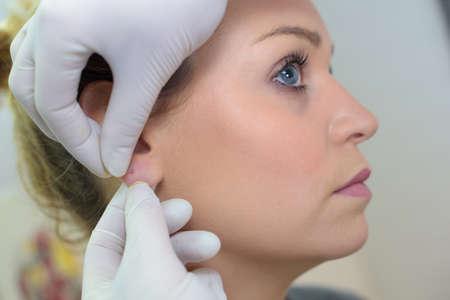having ear pierced Stock Photo