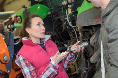 mechanician: young worker checks the pressure of the tractor engine Stock Photo