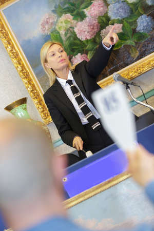 bidder: female auctioneer directing the bids