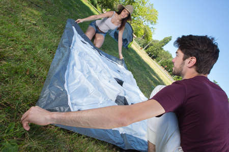 happy young couple setting up their tent at camping site
