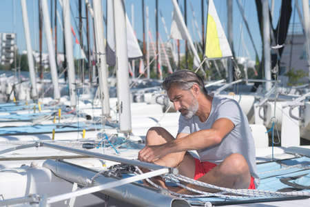 attractive sailor rigging hobbie-cat before sailing course Stock Photo