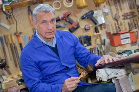 portrait of retired carpenter sitting at his workshop Banco de Imagens