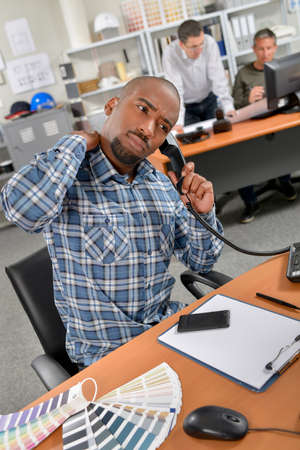 back rub: man on the phone with aching back Stock Photo