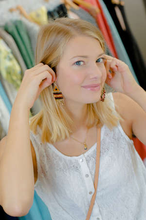 coathanger: Young woman trying on earrings