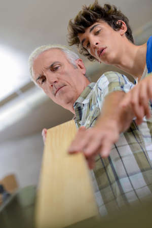 anti noise: Carpenter teaching a young intern Stock Photo