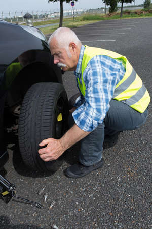 constancy: aged man changing leaking tire on the verge