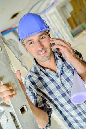 Builder on telephone, holding stepladder Stock Photo