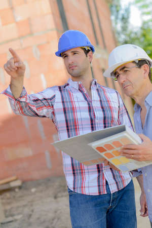 Two men looking at folder of exterior finishings Stock Photo
