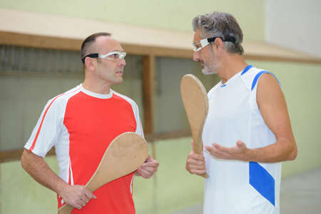 Sportmen in discussion, holding wooden rackets