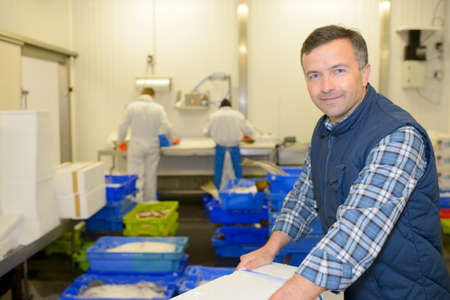 Worker in fish processing plant Stock Photo