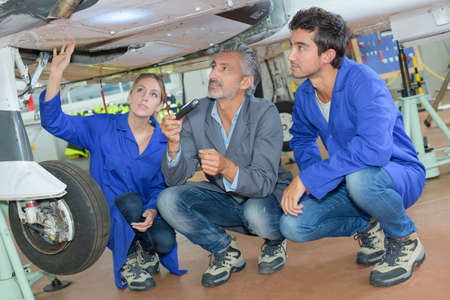 undercarriage: People looking at aircraft undercarriage