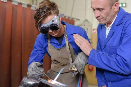 blowtorch: Supervisor guiding apprentice using blowtorch