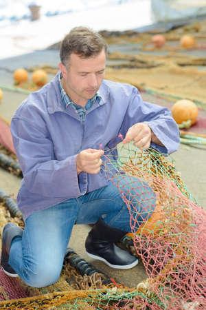 untangle: Fisherman inspecting nets Stock Photo