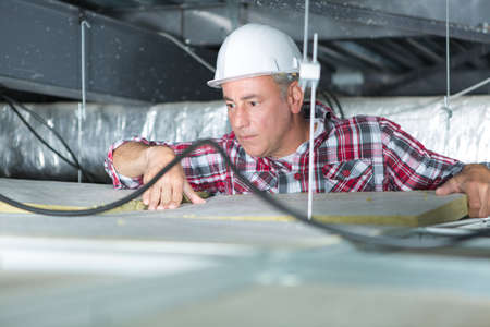 electrician fixing neon on the ceiling Stock Photo