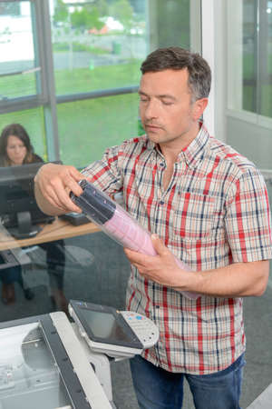 xerox: Man at photocopier holding package