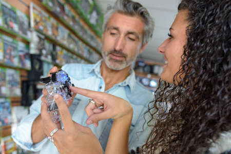 Saleswoman advising man on gaming equipment Stock Photo