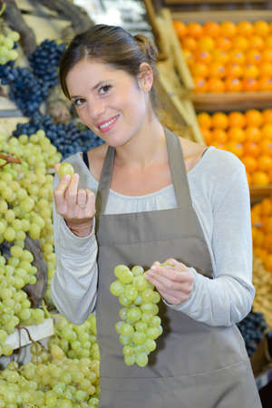 Shop assistant tasting a grape
