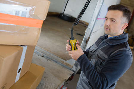 truck driver: delivery man with parcel near cargo truck shipping service