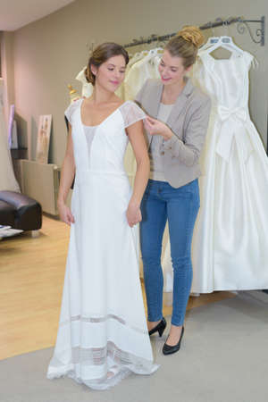 Woman trying on wedding gown Stock Photo