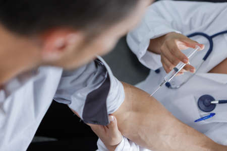 doctor injection flu vaccine to patients arm Stock Photo