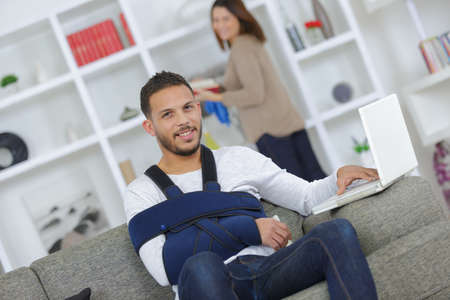 Man with arm in sling using computer left handed