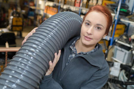 Woman carrying length of pipe Stock Photo