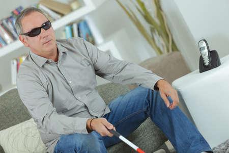 Aveugle assis à la maison avec un bâton