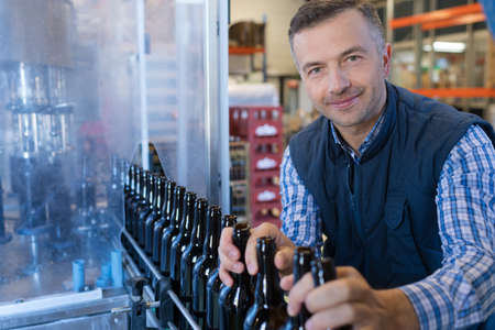 operative: Man overseeing bottling plant Stock Photo