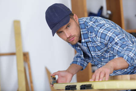 picture of young man working as carpenter and measuring board Stock Photo
