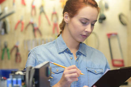 metalic: Young lady in workshop holding clipboard