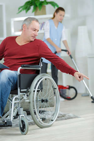 vaccuum: Man in wheelchair pointing to cleaner Stock Photo