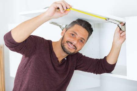 fitted unit: man measuring cupboard door