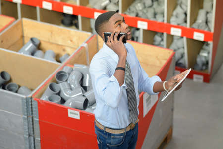 communication industry: Man in pipe fittings department, holding tablet and speaking on telephone