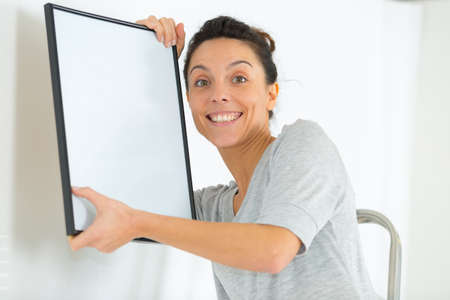 portrait of woman hanging blank picture frame on wall Stock Photo