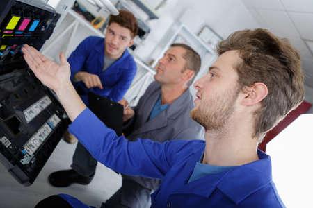 Three men looking at ink cartridges in photocopier Фото со стока