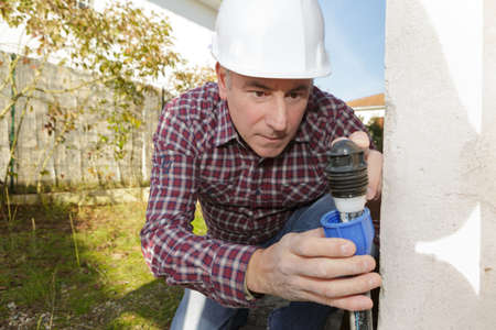 builder installing a water pipe outdoors Stock Photo