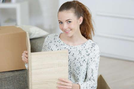 Young smiling woman repairing door of wooden cupboard furniture