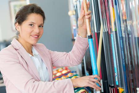 Woman presenting rack of snooker cues