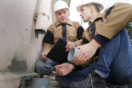 sink drain: checking waste pipe outside of the building Stock Photo