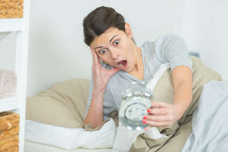 woman in bed looking at alarm clock with shocked expression Stock Photo