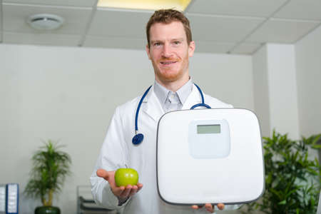 cheerful mature doctor holding a weight scale and an apple
